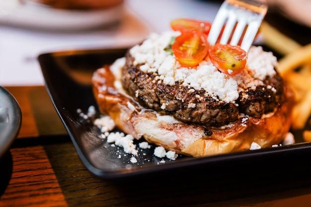Close-up vork prikken cheeseburger met gegrild vlees