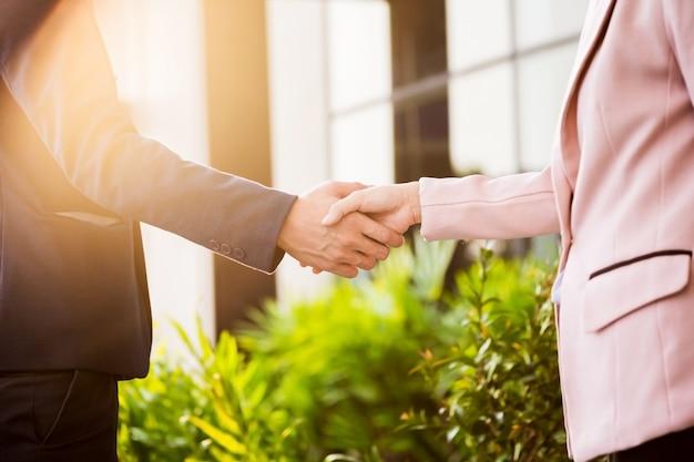 Close-up vriendelijke ontmoeting handdruk tussen zakenvrouw en zakenman met zonlicht.