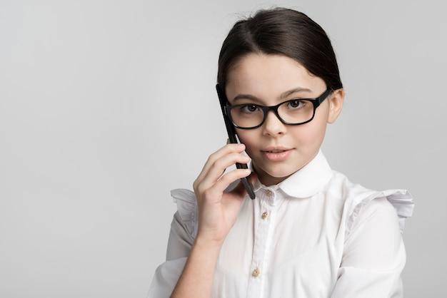 Close-up vrij jong meisje dat op mobiele telefoon spreekt