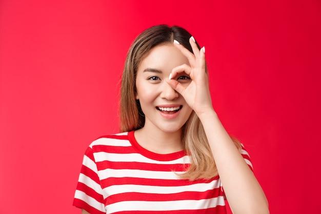 Close-up vrolijk positief aziatisch meisje kijkt door ok teken glimlachend in het algemeen geniet van positieve vibes oordelen...