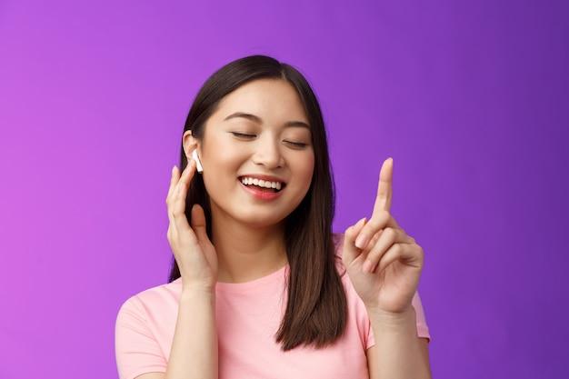 Close-up vrolijke blije aantrekkelijke aziatische vrouw sluit ogen die één vinger opsteken, wachtend refrein, glimlachend opgetogen aanraking draadloze oortelefoon, volume luider maken tevreden genieten van liedjes, paarse achtergrond