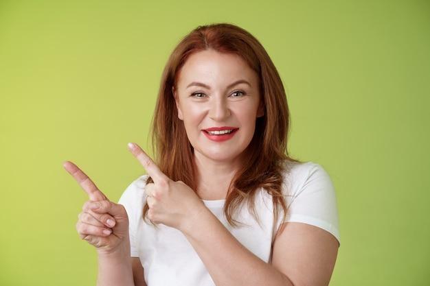 Close-up vrolijke gemotiveerde aangename roodharige vrouw van middelbare leeftijd wijzende linkerbovenhoek wijsvingers glimlachend opgetogen advies geven