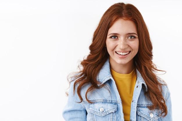 Close-up vrolijke mooie roodharige vrouwelijke student met sproeten in spijkerjasje over geel t-shirt, vrolijk en ontspannen glimlachend, staande terloops witte muur geniet van studeren in het buitenland