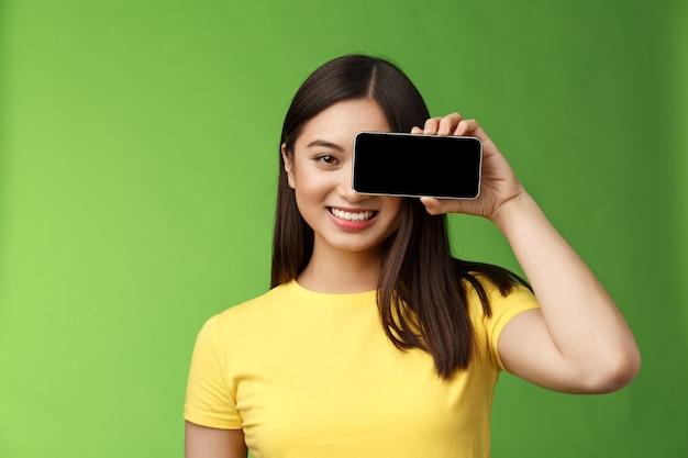 Close-up vrolijke optimistische aziatische vrouw promoot smartphone app houd telefoon in de buurt van eye gaze camera tevreden, glimlachend breed introduceren spel, coole nieuwe applicatie, staan groene achtergrond