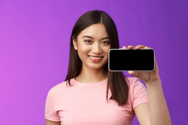 Close-up vrolijke schattige aziatische vrouw houdt smartphone horizontaal, toont telefoonscherm, introduceert geweldige nieuwe applicatie, speelt interessant telefoonspel, staat paarse achtergrond promoot