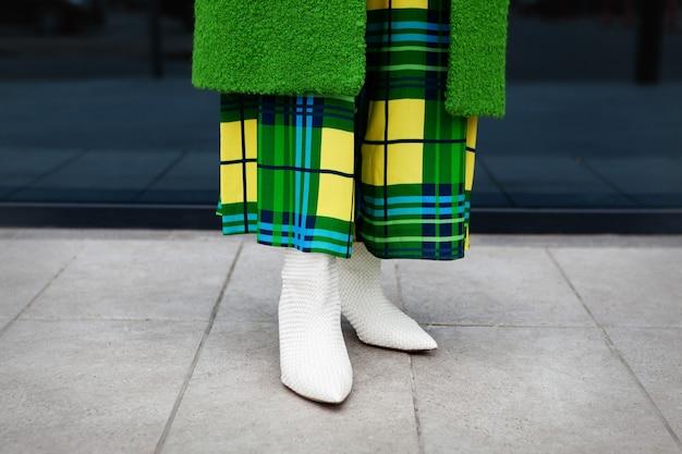 Close-up vrouw benenstijlvolle groene jas gele geruite jurk lederen witte schoenen met hakken
