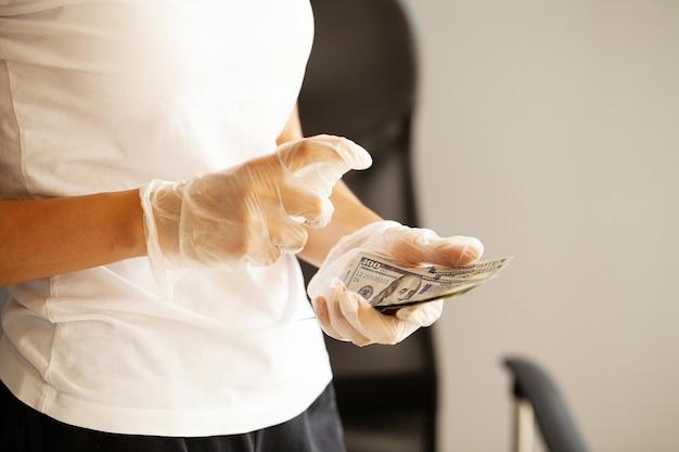 Close-up vrouw desinfecteren geld met antisepticum.