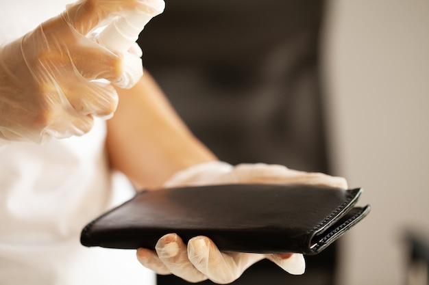 Close-up vrouw desinfecteren portemonnee met antisepticum.