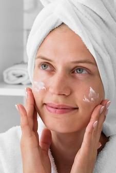 Close-up vrouw die gezichtscrème gebruikt