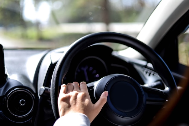 Close-up vrouw die het stuur van een auto vasthoudt, ze bestuurt een auto voor een reis naar het platteland, ze houdt het stuur vast om de auto te besturen en is van plan veilig te rijden.
