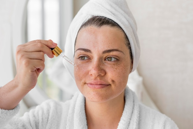 Close-up vrouw die serum gebruikt