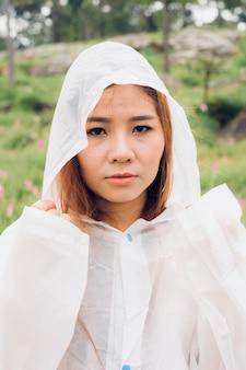 Close-up vrouw dragen regenjas stand in het regenwoud