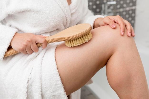 Close-up vrouw haar been borstelen