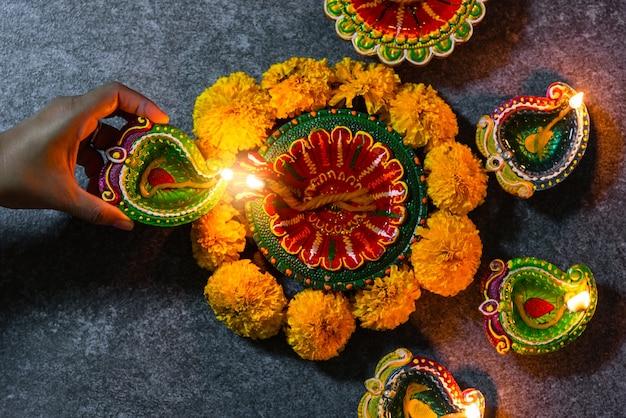 Close-up vrouw hand wordt aangestoken klei licht vuur op diya of olielamp