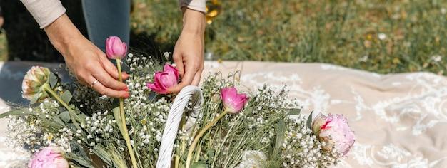 Close-up vrouw handen aanraken en regelen van roze tulpen en wilde witte bloemen in een mand op een gespreide deken op het gras. horizontale banner of koptekst.