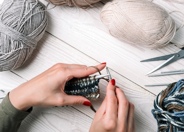 Close-up vrouw handen breit van kleurrijke draden winterkleren