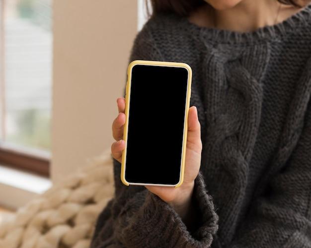 Close-up vrouw in gezellige kleding met nlank telefoon