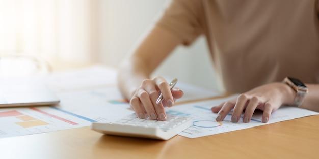 Close-up vrouw met behulp van rekenmachine en laptop, documenten lezen, jonge vrouw die financiën controleert, rekeningen of belastingen telt, online bankdiensten.