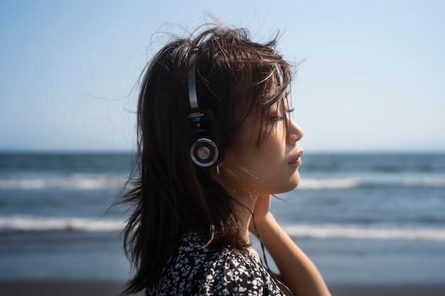 Close-up vrouw met koptelefoon op strand