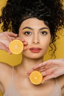 Close-up vrouw met plakjes citroen