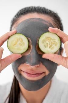 Close-up vrouw met plakjes komkommer