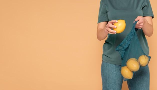 Close-up vrouw met schildpad tas met citroenen