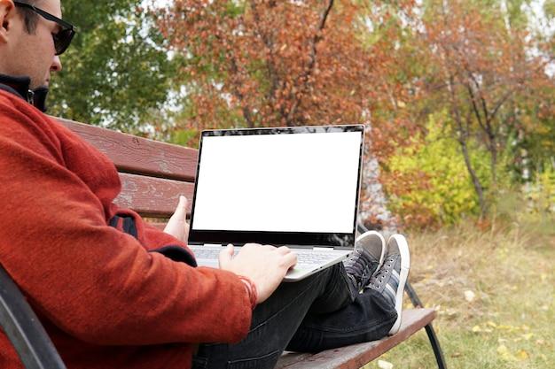 Close-up vrouw zitten in het park bij zonsondergang en met behulp van laptopcomputer. vrije mensenreiziger met ultrabook op de bank die het beeldscherm bekijkt. leeg scherm voor ontwerp.