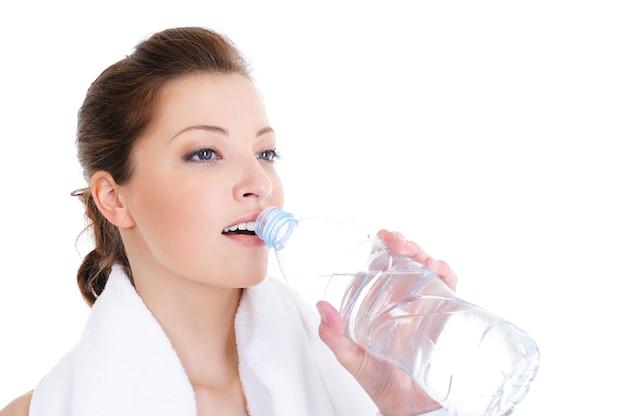 Close-up vrouwelijk gezicht met fles water op wit wordt geïsoleerd