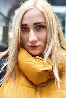 Close-up vrouwelijk portret van een charmante lachende jonge vrouw met blonde haren camera kijken