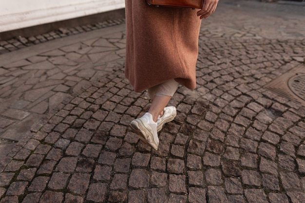 Close-up vrouwelijke benen in modieuze lederen jeugd sneakers lopen op oude stenen weg. trendy meisje in elegante lange jas in broek in stijlvolle schoenen loopt op straat. casual schoenen voor dames in de lente