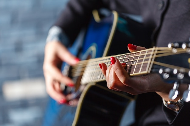 Close-up vrouwelijke hand spelen op akoestische gitaar.