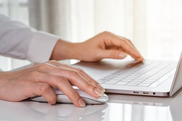Close-up vrouwelijke hand van zakenvrouw met behulp van muis om te werken met een laptopcomputer