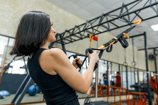 Close-up vrouwelijke handen met fitness riemen in de sportschool