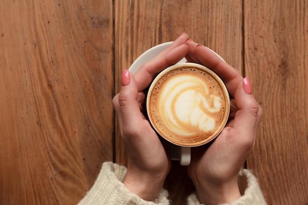 Close-up vrouwelijke handen met kopje koffie cappuccino met schuim met mooi patroon. perfecte rode gellak manicure. houten natuurlijke vintage tafel. creatieve kleur warme nabewerking