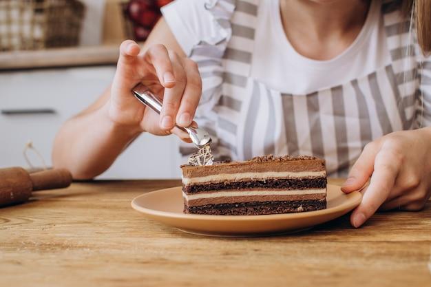 Close-up vrouwelijke handen versieren een chocolade brownie of cake het werk van een banketbakker