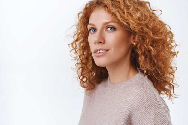 Close-up vrouwelijke prachtige roodharige krullende vrouw in beige blouse staande half omgedraaid over witte muur, draai het hoofd naar de camera met sensuele, vrolijke en kokette uitdrukking, flirten