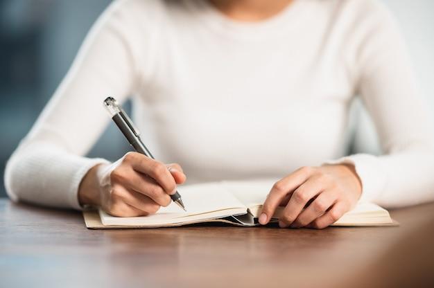 Close-up vrouwelijke student zit voor examen aan universiteitsklasstudenten zitten in de rij onderwijs levensstijl universiteitscollege