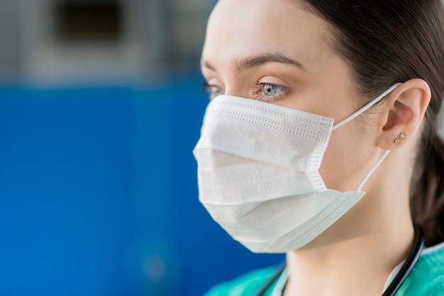 Close-up vrouwelijke verpleegster die masker draagt