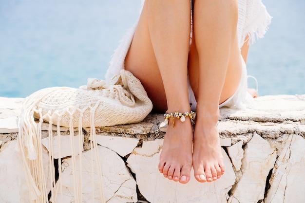 Close-up vrouwenbenen met armband aan de kust at