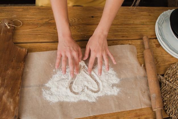 Close-up vrouwenhanden tekenen een hart van meel reclame voor een bakkerij of banketbakkerij