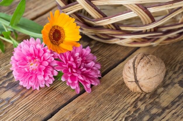 Close-up walnoot, calendula en aster bloemen, rieten mand op oude houten planken. ondiepe scherptediepte. bovenaanzicht.