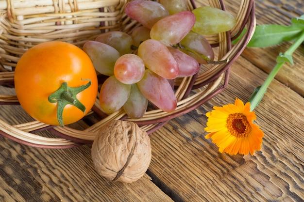 Close-up walnoot, tomaat, calendula bloemen en rieten mand op oude houten planken. ondiepe scherptediepte. bovenaanzicht.
