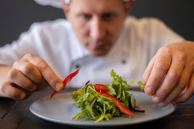 Close-up wazige chef-kok voorbereiding schotel