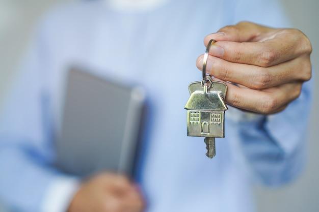 Close-up weergave makelaar makelaar huis sleutelhanger te houden