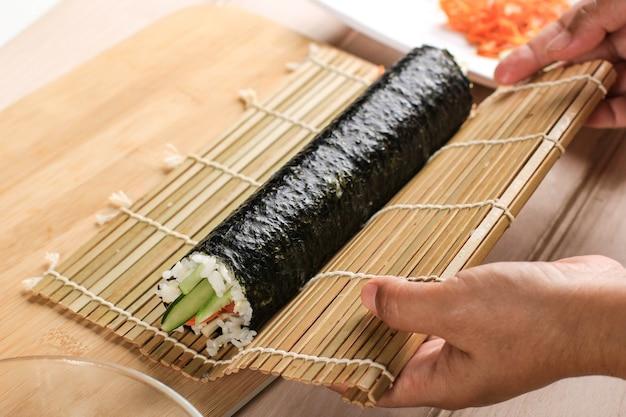Close-up weergave proces voor het bereiden van rollende sushi/gimbap/kimbap. nori en witte rijst. chef's hands touch roll rijst. chef finish kimbop maken of koken