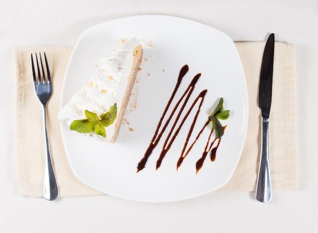 Close-up weergave van gastronomische plakje zoete cake met groene bladeren op de top van slagroom, bereid op een witte plaat en geserveerd op tafel met gebruiksvoorwerpen aan de zijkanten.