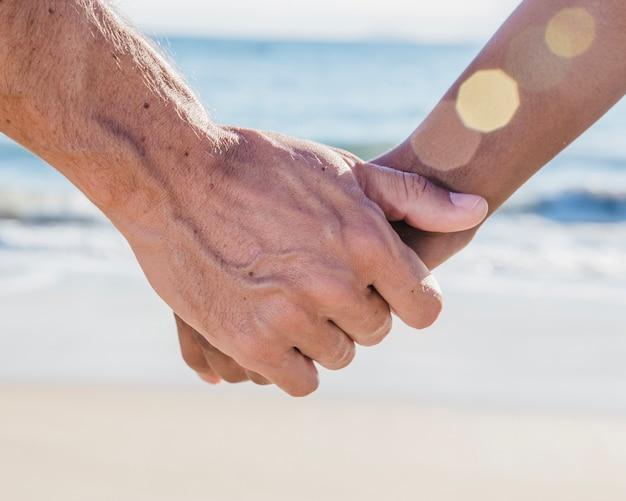 Close-up weergave van paar hand in hand op het strand