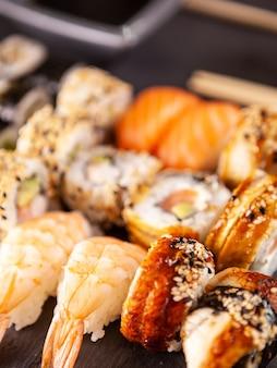 Close-up weergave verscheidenheid aan sushi op zwarte stenen achtergrond