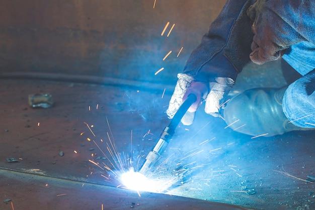 Close-up werk metaal inert gas (mig) lassen of metalen plaat koolstofstaal lassen aan structuur. het proces kan halfautomatisch of automatisch zijn.