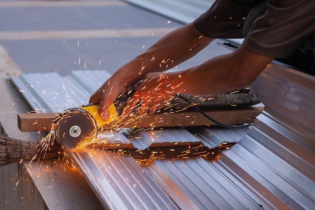 Close-up werknemer gebruik elektrische staal snijder machine.